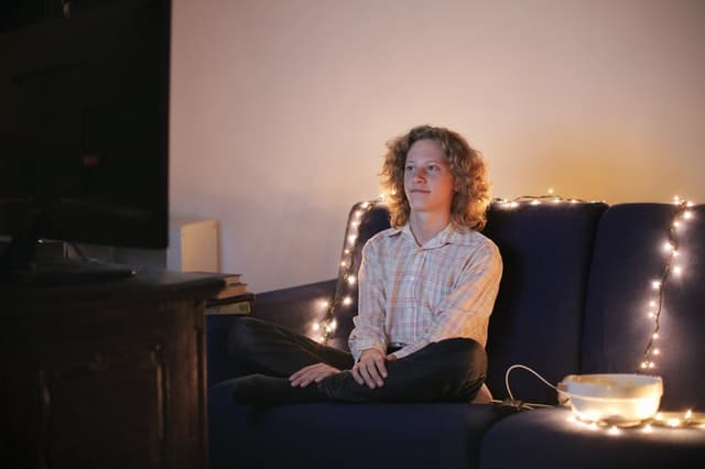 Man watching a tv on his couch surrounded by decorative lights.