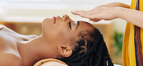 Woman relaxing while enjoying her Reiki therapy.