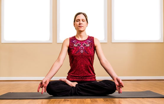 Woman meditating on a yoga map.